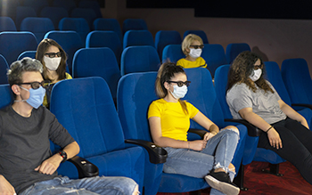 Group of people in the theaters with covid-19 safety regulations.