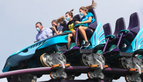 Guests riding on a roller coaster while having their masks on.